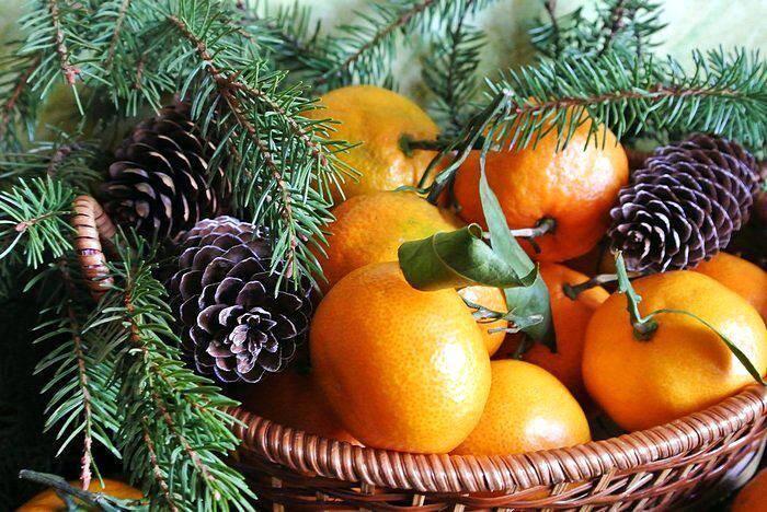 Веточки хвои и мандарины на новогоднем столе
