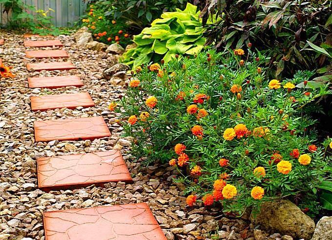 Тротуарная плитка на садовой дорожке из щебня